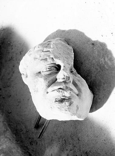 Statue en pierre : tête d'homme mutilée