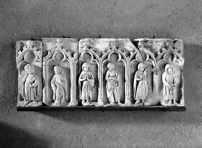 Soubassement de tombeau (supposé) en pierre : personnages debouts sous arcature trilobée