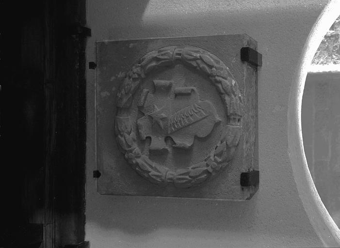 Pierre sculptée : écusson entouré de feuilles de lauriers