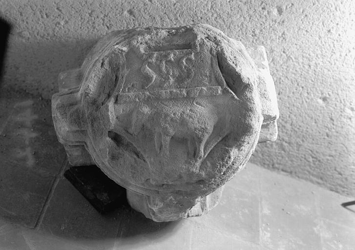 Clef de voûte en pierre avec animaux : agneau surmonté de trois dauphins