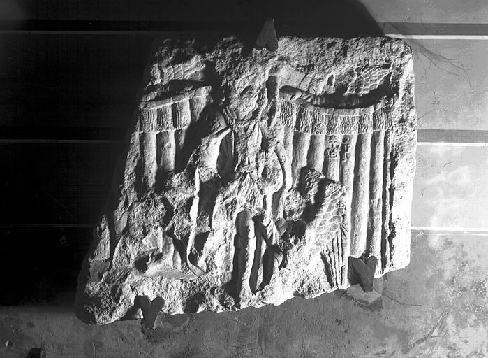 Chapiteau (supposé), relief en pierre : personnage assis avec à ses pieds les restes d'un oiseau