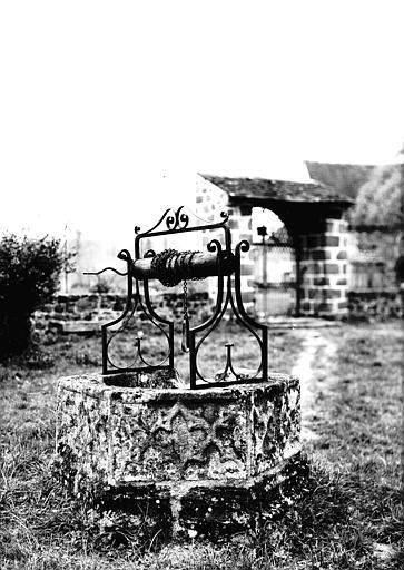 Puits : margelle en pierre sculptée, treuil en fer forgé