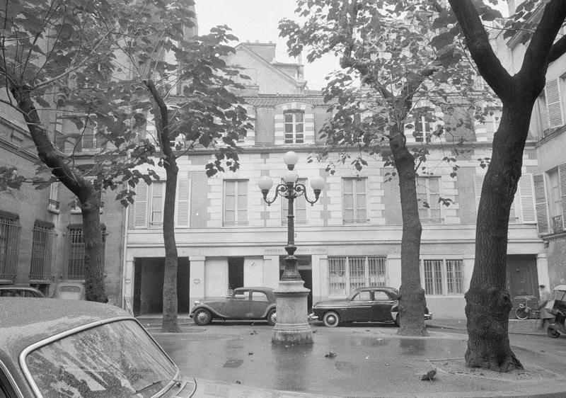 Façades sur place centrale avec lampadaire et voitures stationnées