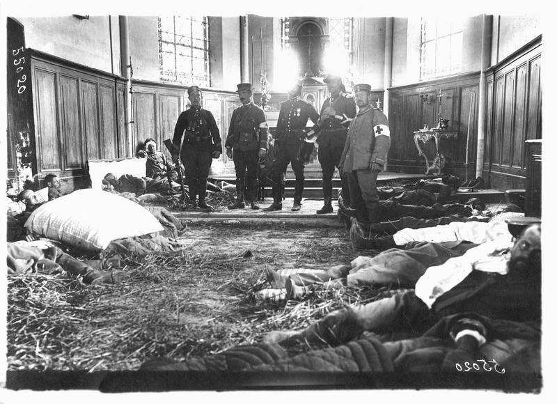 Dans la Marne. Blessés français et allemands allongés sur de la paille, dans l'église de Neufmoutiers