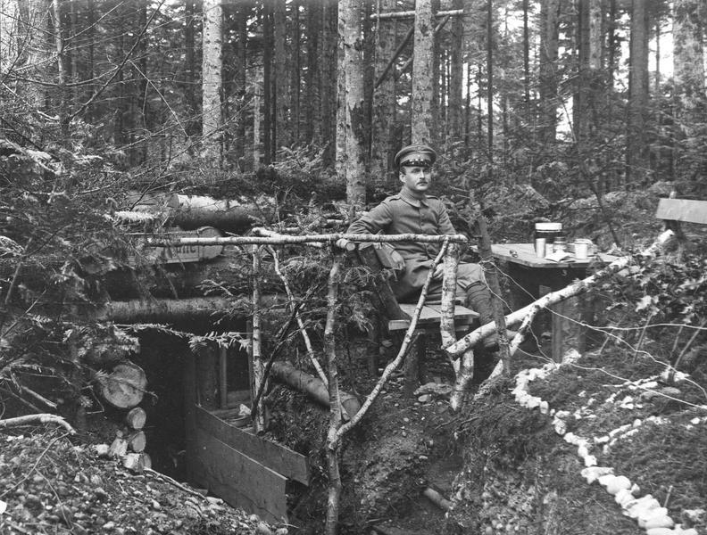 Abri d'officiers à l'arrière du front dans un bois, devant lequel se trouve un poste de repos avec table et banc