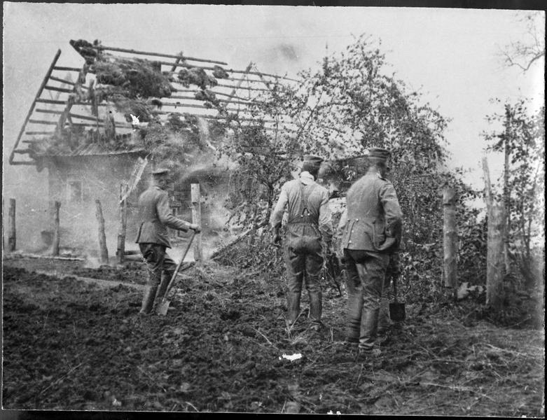 Soldats allemands dans un village incendié de Pologne