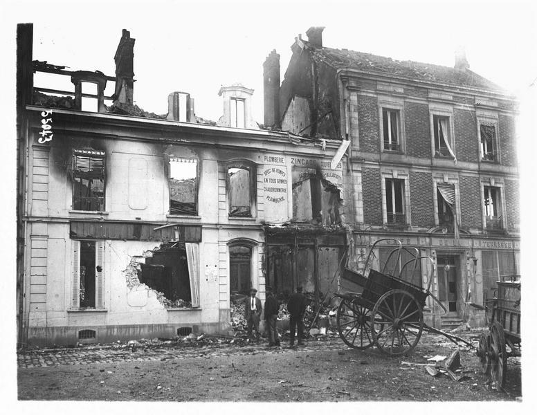 Dans la Marne. Façades détruites et attroupement, deux carrioles