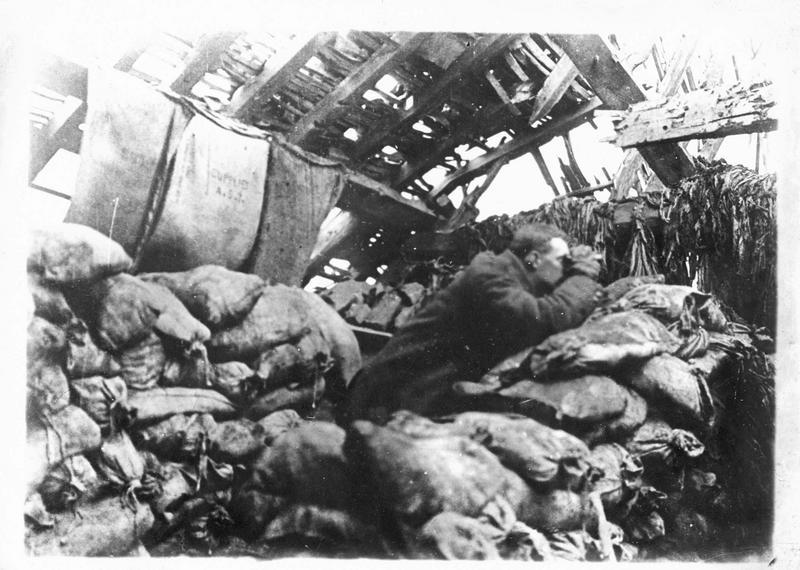 Sur le front. Observateur dans un abri fortifié, surveillant l'efficacité des tirs de l'artillerie à l'aide de jumelles