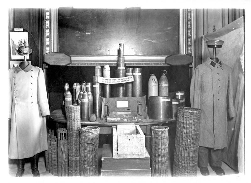 La guerre européenne. Exposition des trophées de guerre au musée des Invalides, dans la salle d'honneur. Tenues d'officier et soldat allemands, spécimens d'obus, boucliers, paniers à munitions etc.