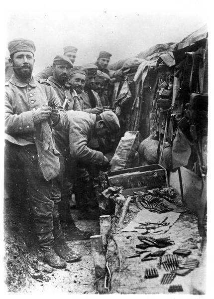 Sur le front. En France. Dans une tranchée allemande, fantassins allemands préparant leurs cartouches et les essuyant avant de les mettre dans le magasin de leur fusil