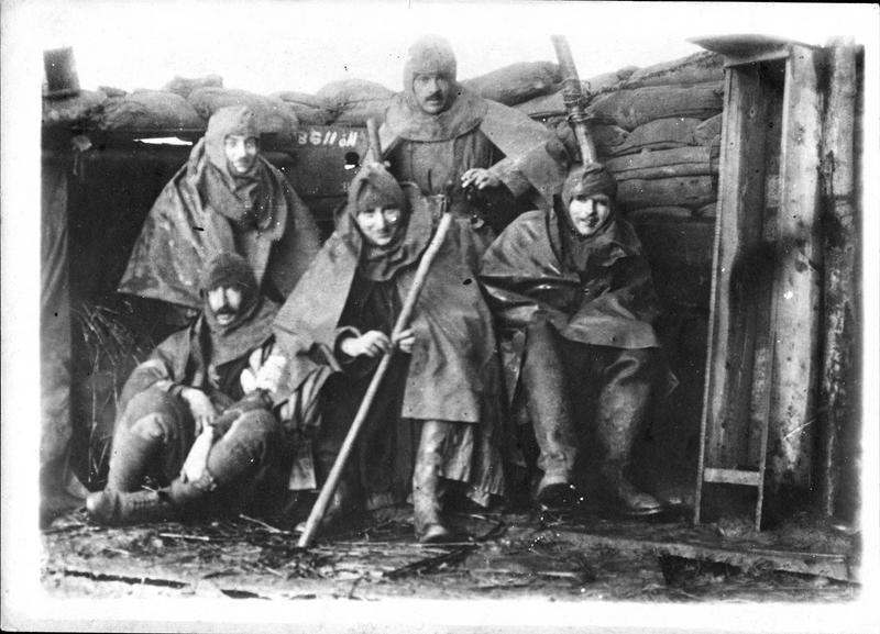 Sur le front. Dans les tranchées, officiers anglais munis du nouvel imperméable et de bottes pour circuler dans les tranchées inondées