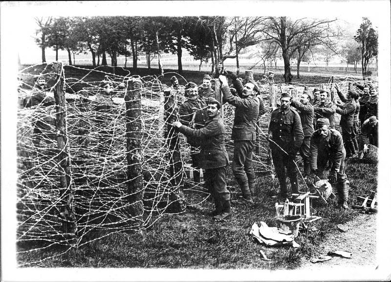 En Angleterre. Soldats anglais construisant une barrière en fil de fer barbelé autour du plus grand camp de concentration des prisonniers allemands (internement de civils allemands), pour empêcher ces hommes de s'évader