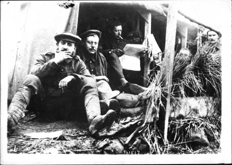 Sur le front. Dans les tranchées abris des Anglais. Pendant que les uns lisent les nouvelles d'Outre-Manche, un camarade joue de l'harmonica.