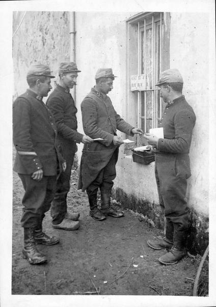 Sur le front. La poste aux armées. Soldats venant déposer dans la boîte aux lettres de fortune la lettre qui réjouira la famille