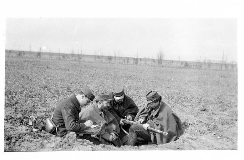 Sur le front. Sur le front champenois. Dans un entonnoir creusé par une marmite, quatre poilus examinent un mauser pris à l'ennemi