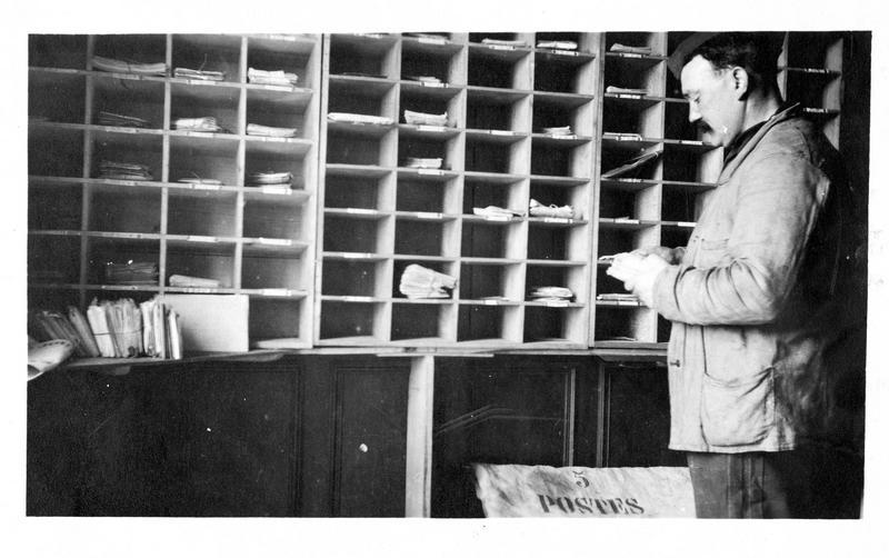 Sur le front. La poste aux armées sur le front. Un bureau postal installé dans une maison abandonnée par ses habitants. Soldats postiers procédant au tri des lettres et envois adressés aux hommes des tranchées
