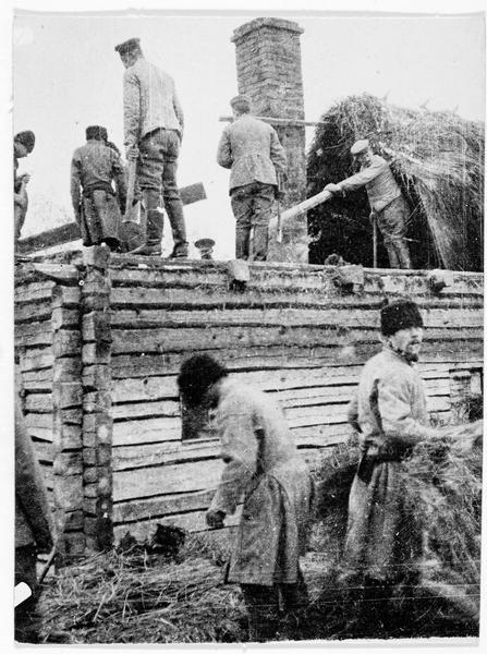 Près de Pinsk, soldats allemands aidant les paysans russes à reconstruire leurs maisons détruites