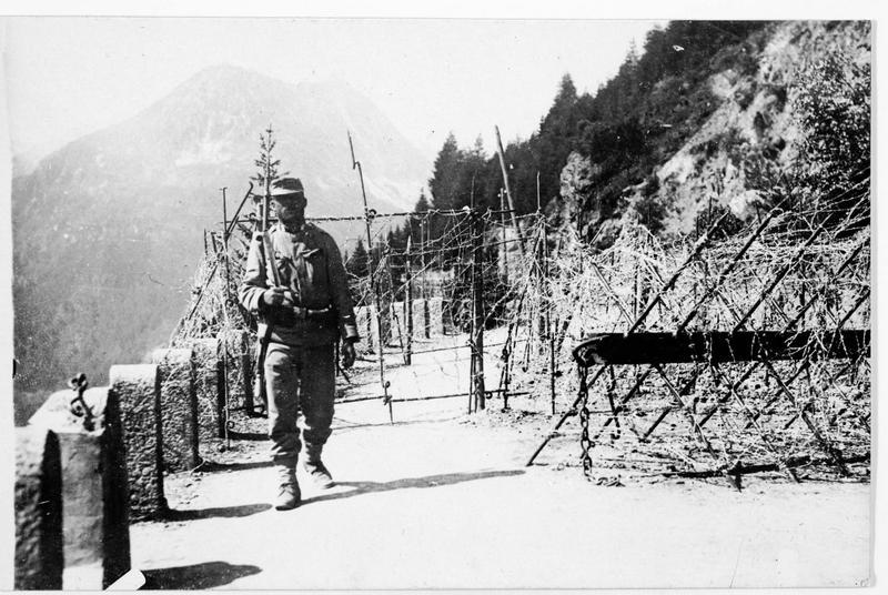 La frontière italienne et un soldat en sentinelle. Route défendue par des chevaux de frise