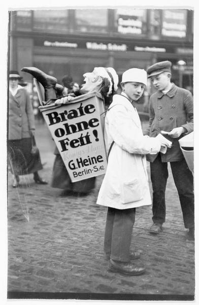 La foire de Leipzig. Les affiches-réclames dans la Peters strasse «Brate ohne Fett! » (frire sans graisse). Jeune garçon avec une marionnette dans sa hotte