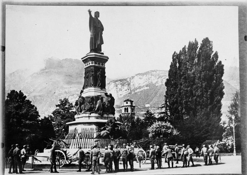 Statue du monument à Dante, avec les armes italiennes capturées (trophées) alignées au pied de la statue