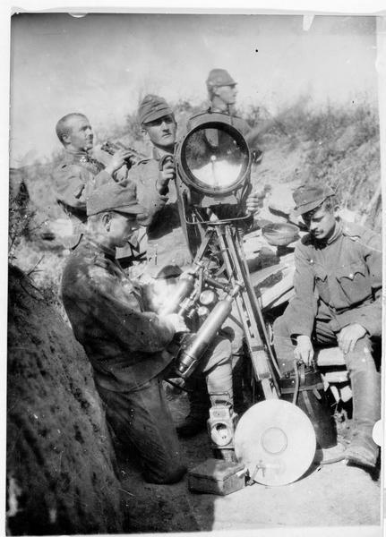 Les moyens techniques de nos alliés austro-hongrois. Projecteur servant à éclairer les positions roumaines. Groupe de soldats en train de nettoyer l'appareil