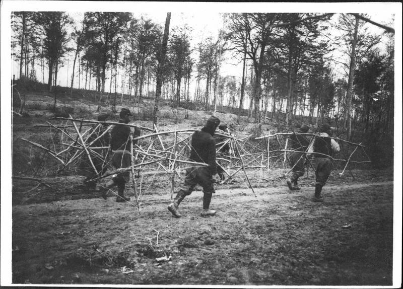 Sur le front. En Argonne, soldats portant des frises en fils de fer barbelés pour protéger leurs tranchées de première ligne
