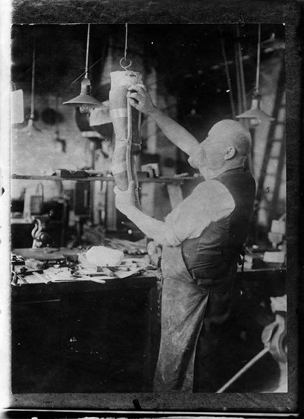 Fabrication d'une jambe articulée [intérieur d'atelier]. Prothèse