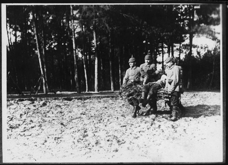 Transport d'un blessé sur des fagots de branches. Brancard