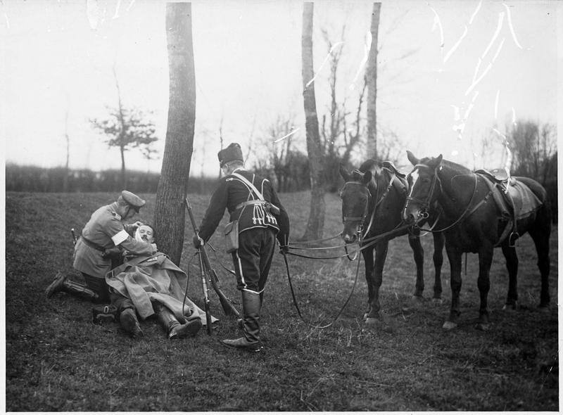 Hussard allemand [et blessé à terre recevant des soins]