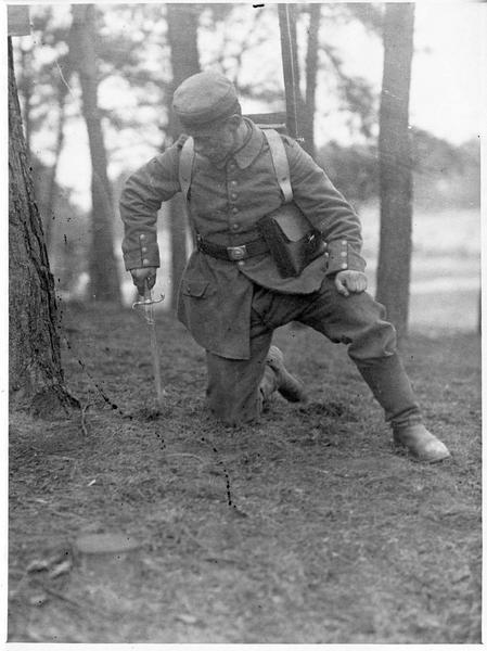 [Soldat allemand plantant un poignard dans un trou dans la terre]