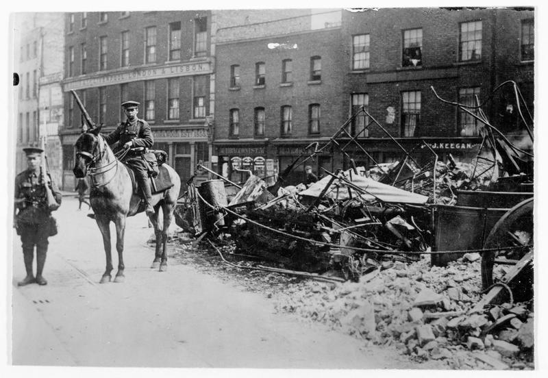 Poste anglais à Liffey street, devant une barricade faite d'une accumulation de tramways électriques