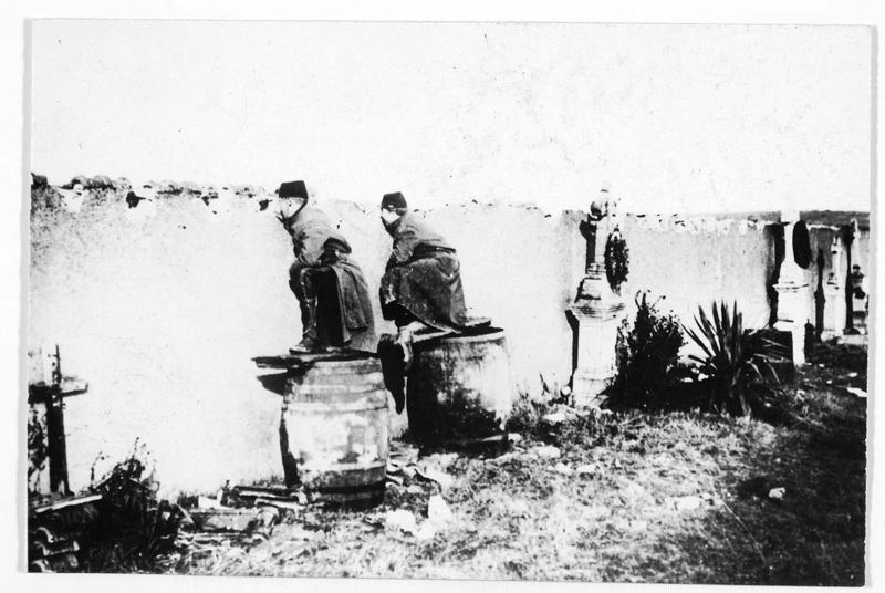 Soldats français en observation derrière le mur du cimetière d'un village