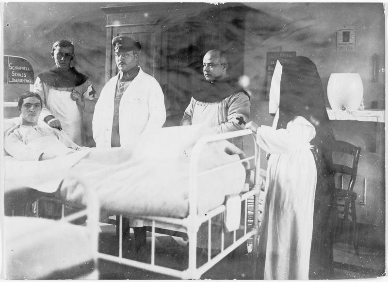 Moines franciscains infirmiers dans une ambulance du front occidental. Un blessé par éclats d'obus allongé dans un lit