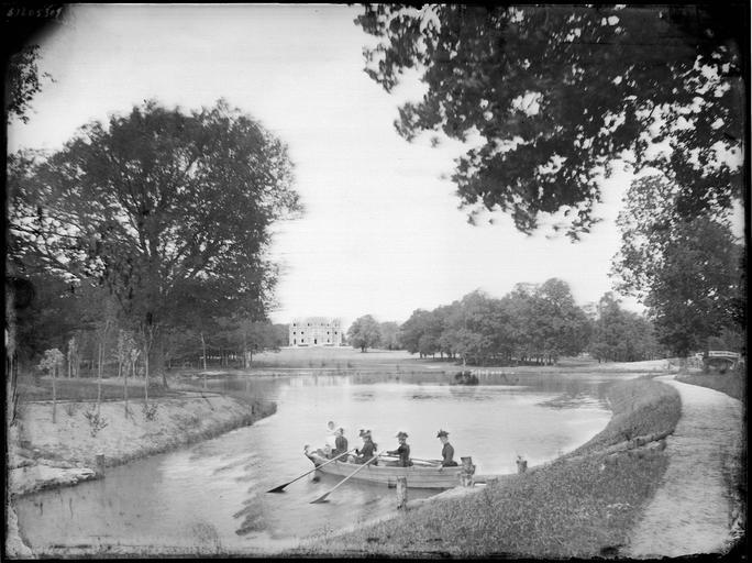 Vue éloignée sur le château, personnes dans une barque sur la rivière