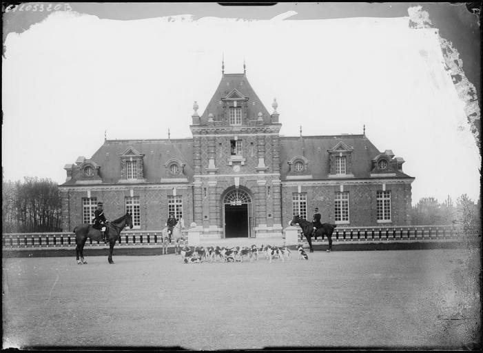 Cavaliers et meute de chiens de chasse devant un pavillon