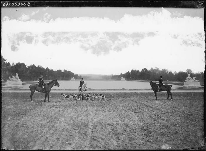 Cavaliers et meute de chiens de chasse devant un bassin