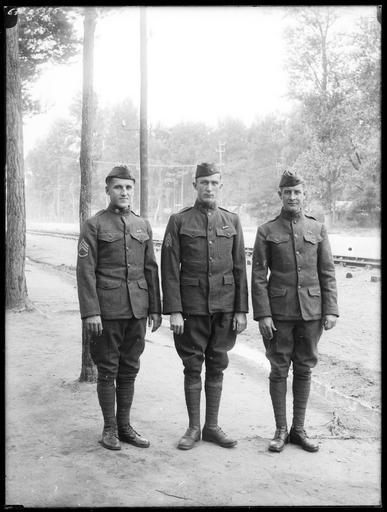 Trois soldats américains devant la voie ferrée