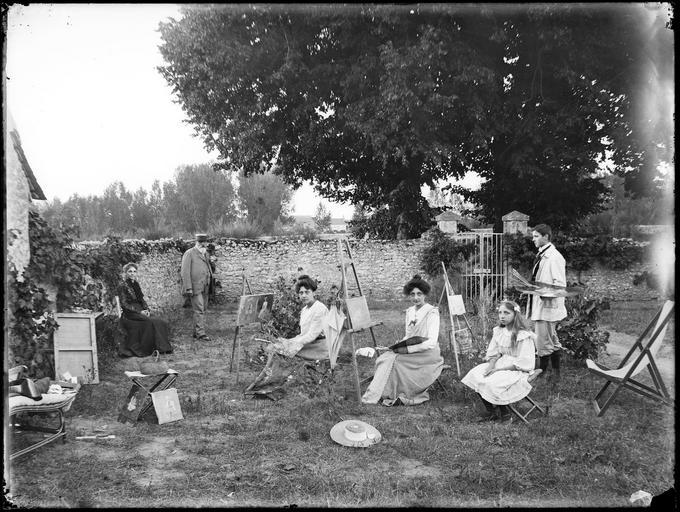 Portrait de famille : les enfants peignant dans le jardin#