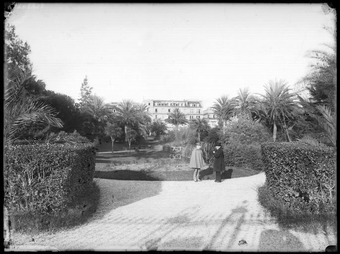 Jardins de l'hôtel et façade, un garde-champêtre et un homme devant des palmiers