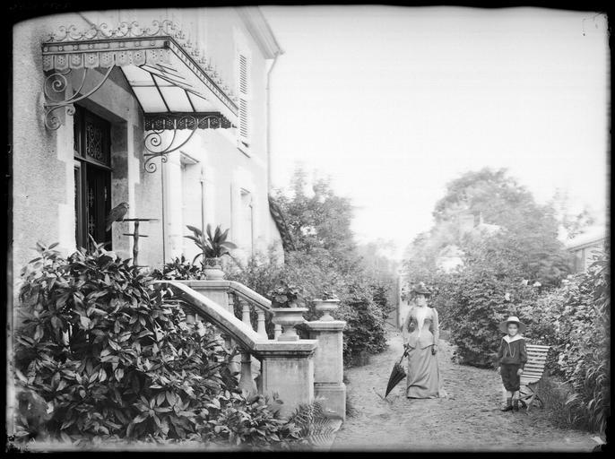 Portrait de sa famille : sa femme et son fils devant l'escalier extérieur#
