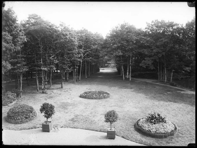 Parc : parterres de fleurs, allée bordée d'arbres