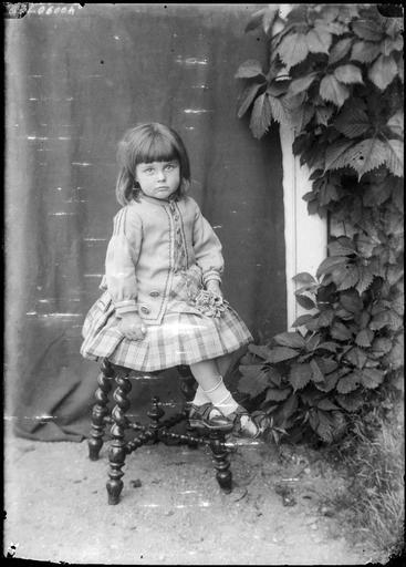 Portrait de sa famille : une fillette assise sur un tabouret#