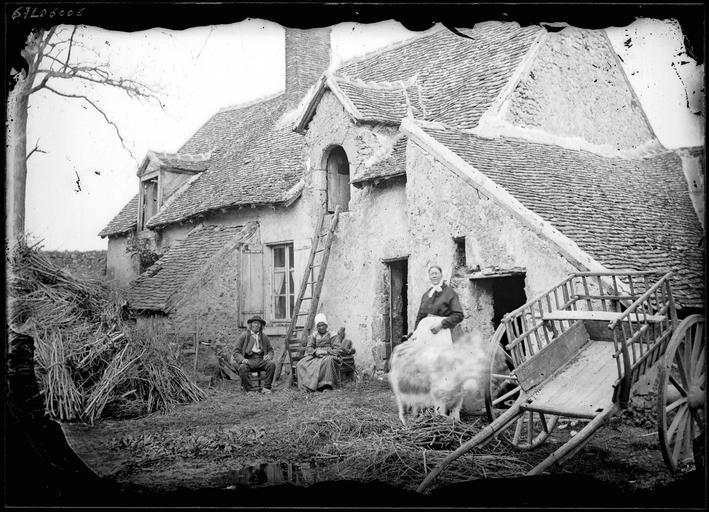 Paysans devant une ferme ancienne, paille et charrette