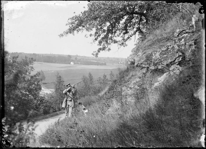 Chasseur avec fusil et son chien dans la campagne