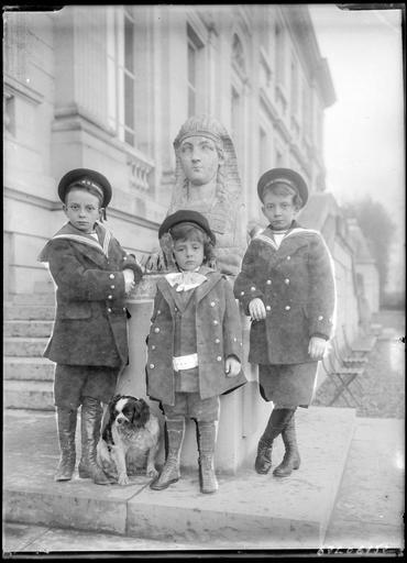 Portrait de trois enfants et un chien devant une sculpture de sphinx