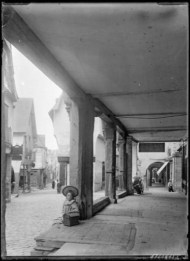 Dans une rue, fillette assise dans une galerie extérieure