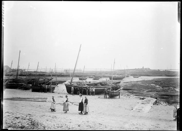 Bateaux échoués sur la grève, bretonnes en costume traditionnel, marins