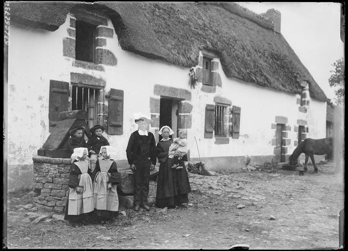 Famille bretonne en costume traditionnel devant un puits