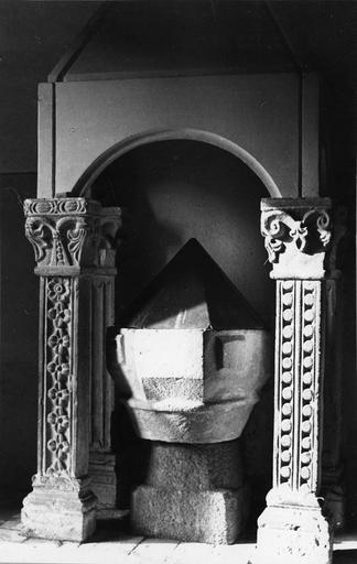4 pilastres à fûts sculptés de motifs différents, surmontés par des chapiteaux feuillagés en pierre sculptée qui supportent un dais de pierre moderne