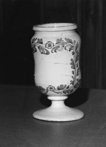 Pot à pharmacie (pot-canon) en faïence à décor de branchages et de fleurettes bleu et jaune sur fond blanc